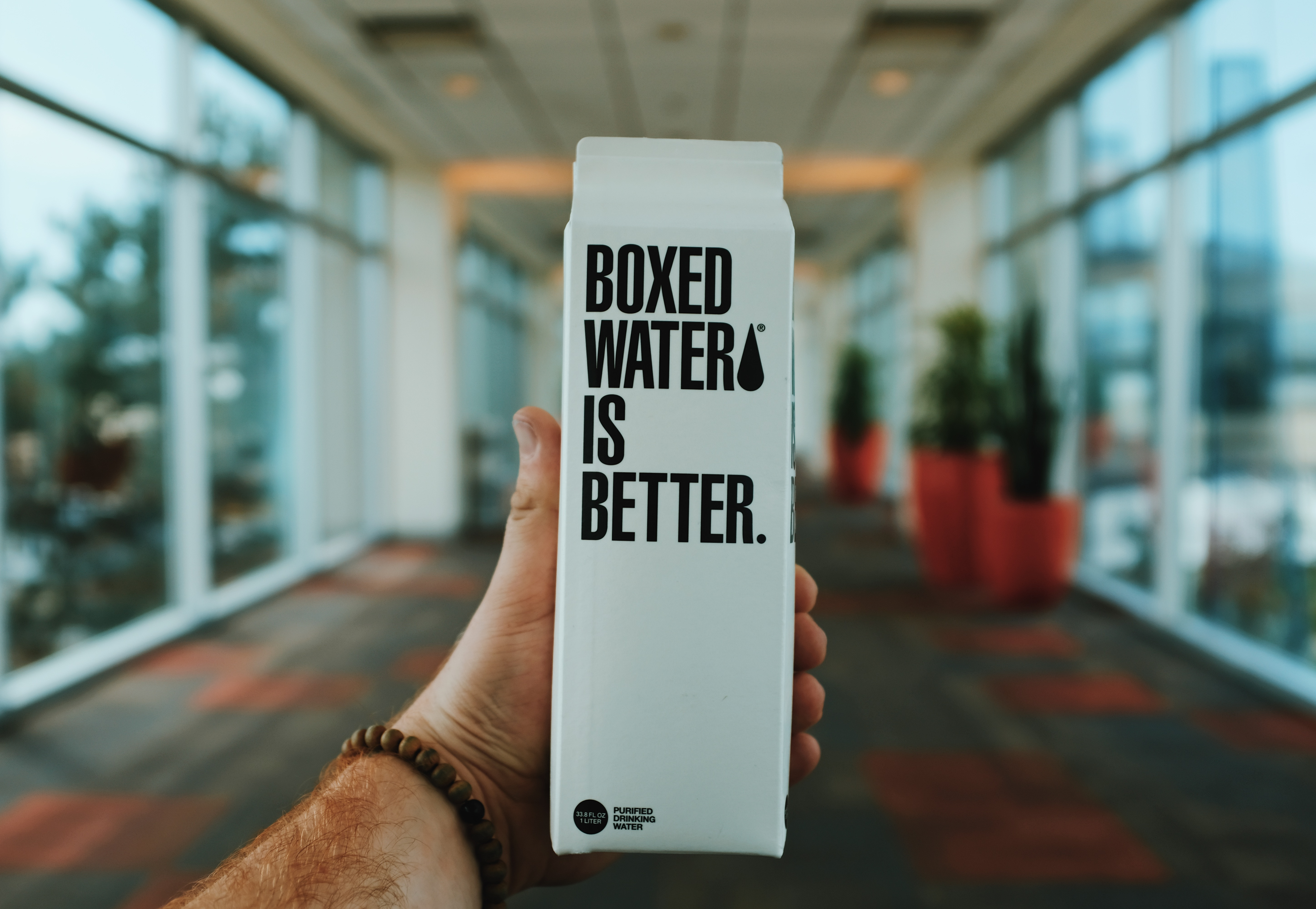 A hand holds Boxed Water, showing a bold statement on the label.