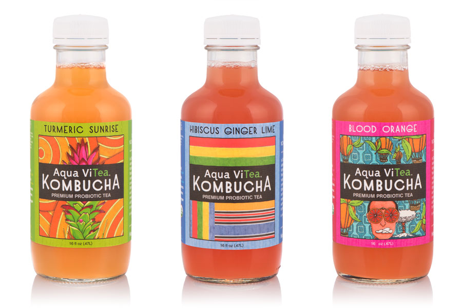 A trio of kombucha bottles with labels.
