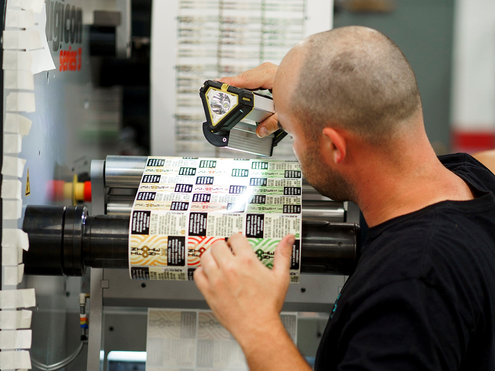 A man examining printed labels for defects.