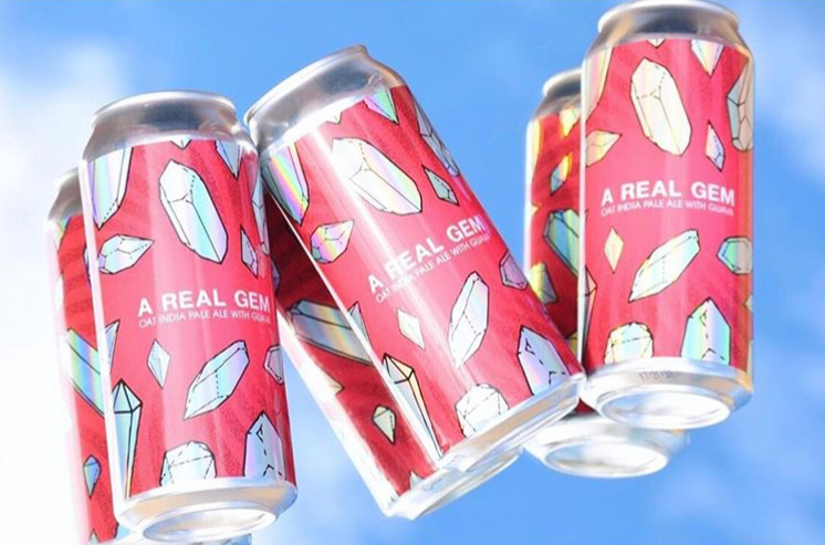 A six-pack of beer with holographic labels.